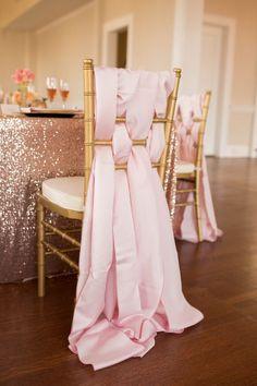 Pink satin sashes weaved through chair back