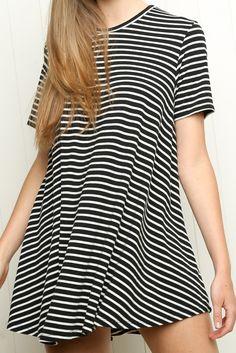 El vestido es blanco y negro. Tiene rayas.