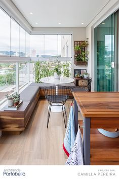 In this apartment balcony, enclosed by glass windows surrounded by an L-shaped wooden bench, the flo Interior Balcony, Apartment Balcony Decorating, Balcony Furniture, Apartment Balconies, Home Decor Furniture, Small Balcony Design, Small Balcony Decor, Home Room Design, Home Interior Design
