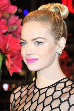 Emma Stone rocking a modern top knot and bright pink lip