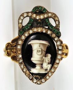 Mourning Ring, c.1780.   Gold, Seed Pearls, green stone, Enamel on Copper.  Initials E.N.  Width: 2 cm.  Place: France.  Period: Louis XV.  Century: 18th century.  Actual Date: c. 1780.   The Bowes Museum.   Museum Accession Number: X.5484