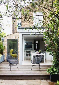 Inodoor outdoor living space with round chairs and views into the kitchen