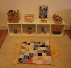 6 month shelf. rattles, bead mazes, music, visual discovery bottles, textural items.