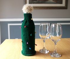 This Christmas Wine bottle cover is knit in the style of a Christmas Tree complete with miniature glittery ornaments/baubles shaped like decorative lights.   This wine bottle bottle cover has a secure knitted base.