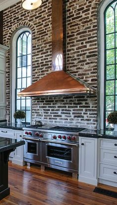 Brick wall, arched windows, wood floor, copper hood and an amazing stove. - Model Home Interior Design Kitchen Dining, Kitchen Decor, Eclectic Kitchen, Kitchen Island, Copper Kitchen, Kitchen Brick, Loft Kitchen, Kitchen Hoods, Kitchen Backsplash