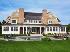 Shingle style with symmetry in Bridgehampton, NY - Boxwoods and potted hydrangeas around the pool - Austin Patterson Disston Architects, featured in Traditional Home Magazine