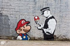 Bansky: Mario and a cope, where the mushroom from Mario is suppose to be a drug. He has used spray paint on a side of a building. Abstract art work style and in the style of graffiti. I have always liked Bansky's work.