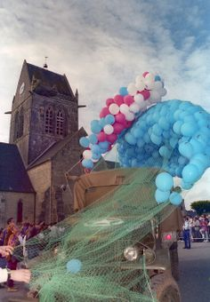 On the 50th anniversary, a World War II-era truck in mint condition is parked in front of the church at St. Mere Eglise with red, white and blue balloons set to be released after 82nd Airborne Division soldiers parachuted onto Amfreville drop zone.