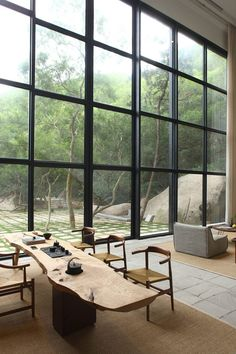"""Designed as a rural """"paradise"""" for a client tired of city life, the Returning Hut in China's Fujian province fosters connection to the surrounding environment through its huge, double-height windows. Loft Interior, Interior Architecture, Interior And Exterior, Apartment Interior, Asian Interior, Natural Interior, Interior Modern, Natural Furniture, Wooden Staircases"""