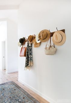 Love the beach-y vibe and laid-back look of this wall! Coat racks are such a great way to get organized.