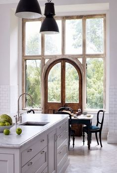 amazing rustic arched door in the middle of a double wall of windows.  No need for artwork. Look outside at God's creation.  LOVE.