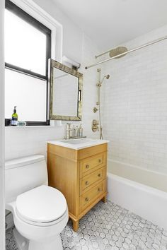 Much like the kitchen, the homeowners wanted cosmetic changes to both bathrooms to reveal more of their personal style and taste, favoring neutral colors and patterns and aiming for a brighter, cleaner feel. A dark wood vanity sink originally stood to the left of the tub but was replaced with a much lighter wood finish with twice the storage space. A chic square mirror with an antiqued bevel stands over it, and new Kohler toilets were added in both bathrooms.