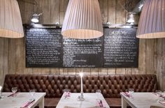 Tufted banquette seating with chalk board & natural wood wall