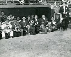 Horizontal black and white photograph of press photographers in the Cardinals' dugout. There team members visible in dugout with them. Spectators in stands in background. Photographers wearing suits and Cardinals are in uniform. Photographer Pete Hangge is seated at far right. Circa 1935-1945.