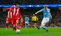 Manchester City's Kevin De Bruyne fires in a shot past Sevilla's Adil Rami and ultimately past the far post.