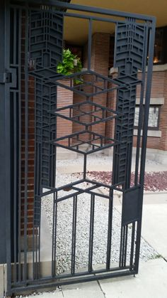 The metal garage entry gates detailed in Frank Lloyd Wrights abstract pattern.