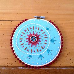 Tableau bohème folk, brodé main feutrine naturelle bleu ciel, pompons prune, cercle à broder