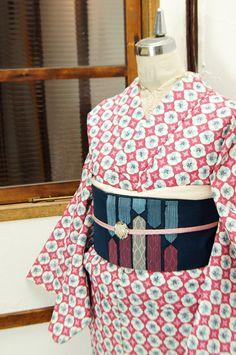 ストロベリーピンクに、花模様が形作るタイルを思わせる水玉パターンがデザインされたウールの単着物です。