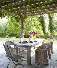On the terrace, a pergola covered in white wisteria shades an outdoor dining area with a reclaimed teak table, a French iron chair, and rattan chairs with Sunbrella cushions, all from Bloom; the paving tile is natural cleft bluestone.