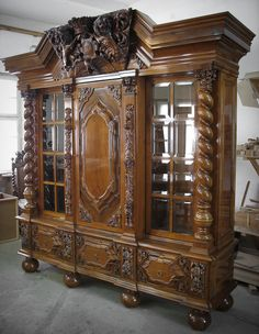 A three-door bookcase. Glazed side door with muntin bars. Middle door: full, with a richly decorated panel and motifs of acanthus leaves in the corners. At the sides of the door there are openwork pilasters with puttoes and acanthus leaves. Three drawers at the bottom. Richly decorated top with a large coat of arms of Gdansk. The surface of the piece of furniture was traditionally finished with a French polish, highlighting the refined natural wood pattern. write us: info@meble.gda.pl