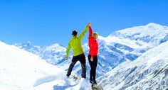 Teamwork motivation couple hikers climbers with arms up fitness and sport woman success in winter mountains. Inspiration beautiful landscape and healthy lifestyle on snow in Himalayas Nepal.