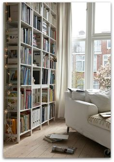 white living room with reading nook and tall bookshelf, floor to ceiling windows