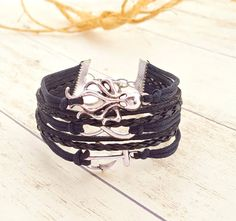 ⚓ Octopus, Infinity, Anchor Charm Bracelet  ⚓ Black Waxed Rope with Black Braided Leather  ⚓ Measures 6.5 inches with a safety chain that extends to 7.5 inches, 1 inch width  ⚓ Finished with a Lobster Clasp and medium grade Stainless Steel Chain  ⚓ Materials are Vegan friendly  ⚓ Items come wrapped in a double layer of tissue paper inside a standard 4 x 8 bubble mailer  ⚓ For more Nautical Bracelets, Click Here... https://www.etsy.com/shop/RiverbendBraceletCo?section_id&#x...