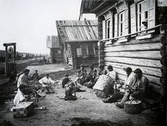 """Old Russian peasant and his job / And some more spoon makers grouped with basket weavers sitting next to traditional """"izba"""" or wooden house - there is also a well on the left."""