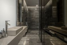 The master bathroom is long and narrow and features floor-to-ceiling mirror panels facing the vanity