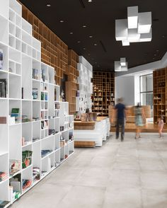 sono architects envelops slovenian bookstore with geometric timber shelving