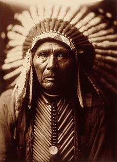 Three Horses, head-and-shoulders portrait, facing front, wearing headdress. Photograph by Edward Sheriff Curtis, ca. 1905.
