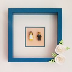 Create a WEDDING TOPPER SHADOW BOX in under half a hour. Find a shadow box in your desired size (available at any craft store or Amazon). You can incorporate your wedding colors by both painting the box and using a colorful cardstock for the insert. Adhere cake toppers to the cardstock. You can also add other wedding day mementos (program, write vows on mat, confetti, favors, garter, dried flowers, etc.) to box. Add embellishments (like the paper flowers) to frame as desired.