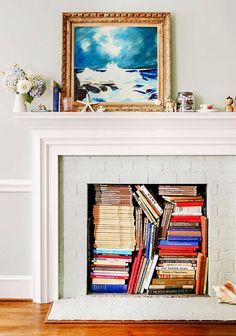 Cool casual idea for a non working unused fireplace. A coastal display... and book storage! Featured on Completely Coastal along with other coastal fireplace decor ideas for your unused non working fireplace.