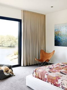 Master bedroom looking out to lake. Butterfly chair in tan leather,Matthew Johnson artwork,Charlie the greyhound in basket! Production –...
