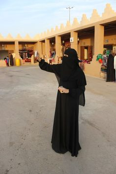Femal expat English teacher in Saudi Arabia taking a selfie in a marketplace. She is fully veiled in hijab, abaya, and niqab