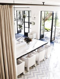 Dining space with steel frame windows, white dining room table, white chairs, beige curtain, and white walls