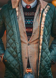 Wear a teal quilted jacket with blue jeans to get a laid-back yet stylish look.  Shop this look for $568:  http://lookastic.com/men/looks/jeans-tie-longsleeve-shirt-crew-neck-sweater-blazer-jacket-belt/4627  — Blue Jeans  — Red Print Tie  — Navy and White Vertical Striped Longsleeve Shirt  — Black Fair Isle Crew-neck Sweater  — Brown Houndstooth Blazer  — Teal Quilted Jacket  — Orange Leather Belt