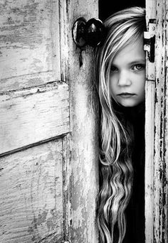 The beauty of this photo to me is the contrast of texture. The weathered, vintage door and jamb are a firm frame to the little girl's soft young skin and her elongated, gentley-curved and slightly unruly strands of hair. [Behind the doors: Portrait Photography Tips and Ideas]
