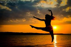 2014 High School Senior girl for posing picture ideas. Senior girl posing in front of a sunset jumping for a ballerina or dance inspiration idea.