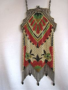 This Mandalian mesh purse is strikingly beautiful all done up in red, black and cream painted patterns of flowers and abstract art deco designs. There are touches green and gold accents as well. This purse boasts a lush fringe complete with five egg shaped black enameled drops.  8.25 x 3.24 inches wide.