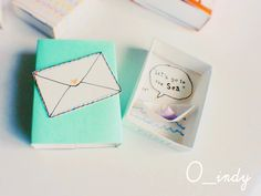 Turquoise matchbox with tiny paper boat.
