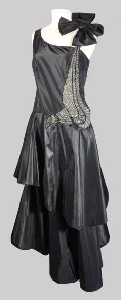 "Evening dress, Lanvin, winter 1928. Model is called ""Beautiful Bird."" Black silk taffeta embroidered with a large pheasant in tiny glass beads & faceted oval & round glass & jet bugle beads."