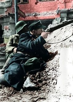 Soldier from the Kiliński Battalion pictured aiming his rifle at the German-occupied PAST building, 20 August 1944