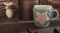 """Porzellantasse mit gehäkeltem Tassenwärmer """"Stern"""" in helltükis-weiß.  Eine schöne Geschenkidee oder ein kleines Mitbringsel.   Der Tassenwärmer ist mit einem Knopf befestigt und kann zum..."""
