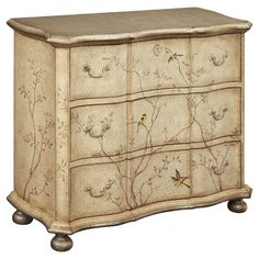 """Three-drawer chest with a textured finish and hand-painted bird motif.   Product: ChestConstruction Material: MDF and poplar woodColor: Endicott  beigeFeatures:  Three drawersHand-painted bird and tree detailsScalloped design Dimensions: 42"""" H x 35"""" W x 18"""" D"""