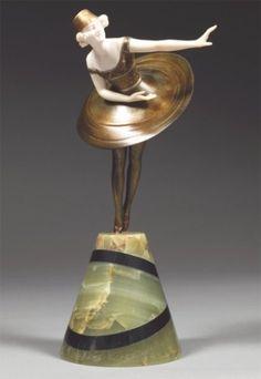 """PROFESSEUR OTTO POERTZEL (1876-1963) """"THE TOP"""" Sculpture chryséléphantine présentant une danseuse animée d'un élégant mouvement, sa jupe circulaire animée d'un mouvement dynamique, un de ses bras tendu venant accentuer l'instantané de la posture, ronze à patine médaille, ornements patinés or et argent. Socle tronconique en onyx, incrusté de deux cercles asymétriques en marbre noir. Signature manuscrite incisée """"Prof. Otto Poertzel"""". 31 cm"""