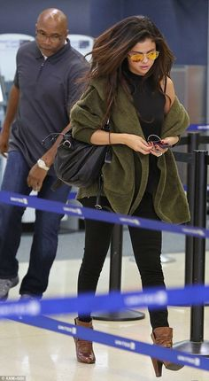 Is that you? Selena Gomez hides behind shades as she arrives in Los Angeles at LAX with help from her bodyguard but was stopped in her track...