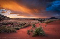 Flaming Namibian Rainfall by Mark Bumbleton.  The last light of day illuminates heavy falling rain in hues of oranges, giving much needed moisture to the barren landscape of the Excelsior Farm in the Namib Rand conservancy, Namibia. The already spectacular landscape of Namibia takes on an even more spectacular mood underneath epic, stormy light.