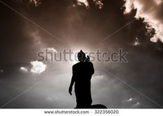 Buddha statue ok sign post bottom view with dark silhouette with deep clear blue sky with few clouds and white light glowing