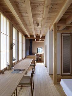 Long wood desk against wall of shoji screens in bedroom of Yatsugatake Villa in…